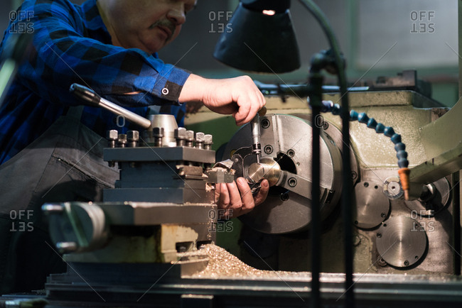 Technician in protective workwear repairing metal in industry