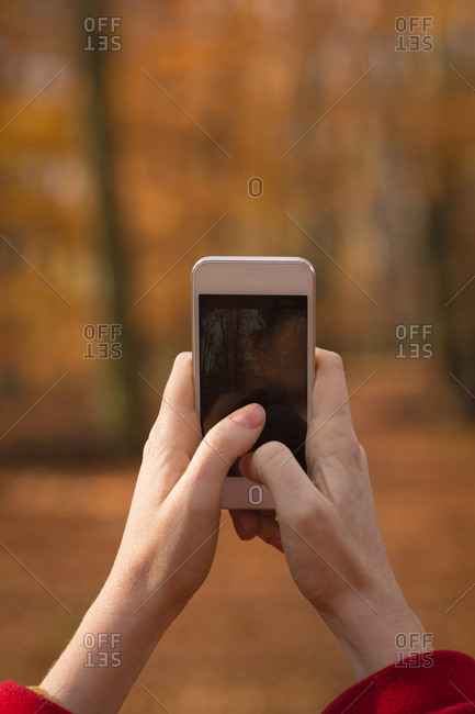 Woman taking photo with mobile phone in the park