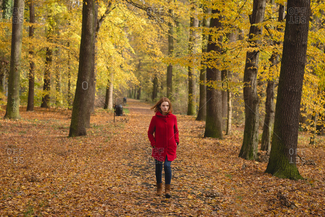 Woman walking alone in the park during autumn