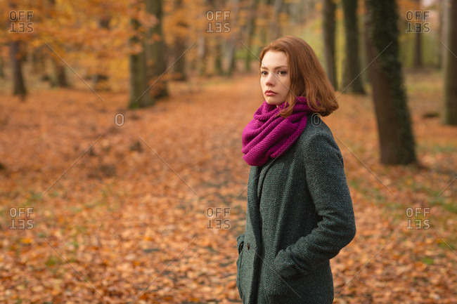 Woman standing with hand in pocket at park during autumn