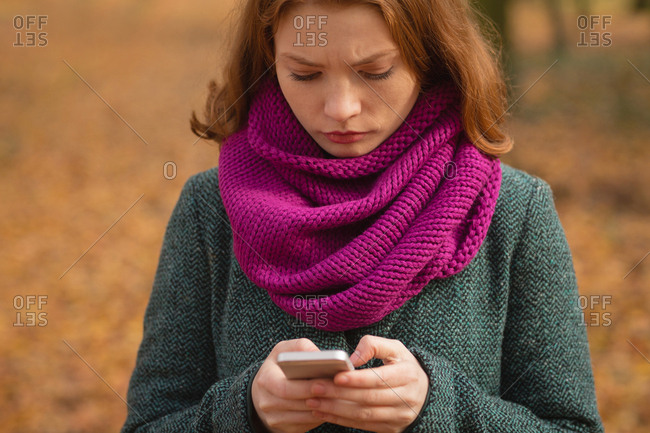 Woman using mobile phone in the park during autumn