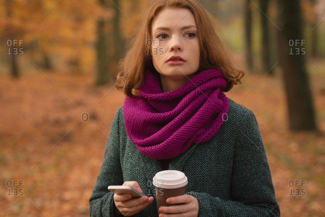 Woman using mobile phone while having coffee in the park