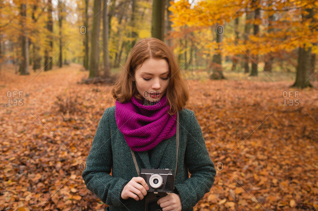 Woman holding vintage camera in the park during autumn