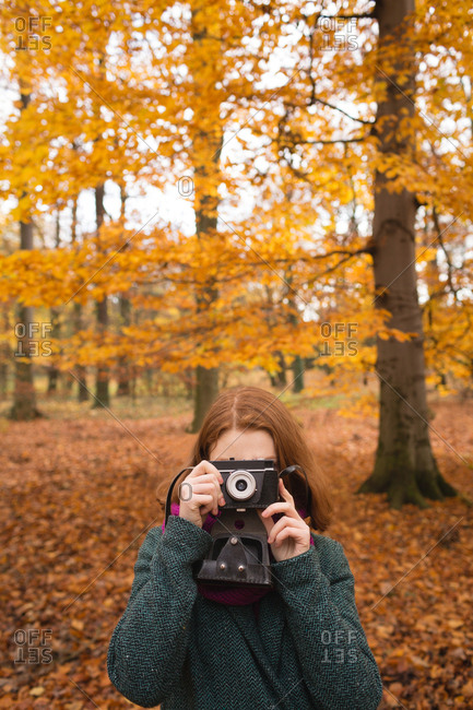 Woman taking photo with vintage camera in the park during autumn