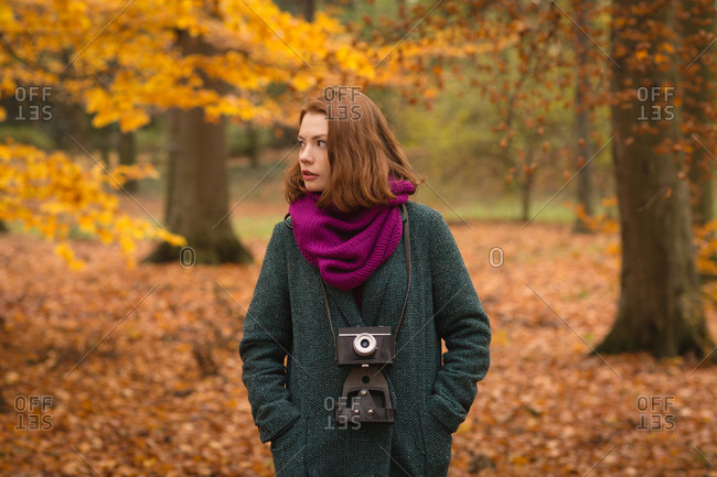 Woman standing with hands in pocket at park during autumn