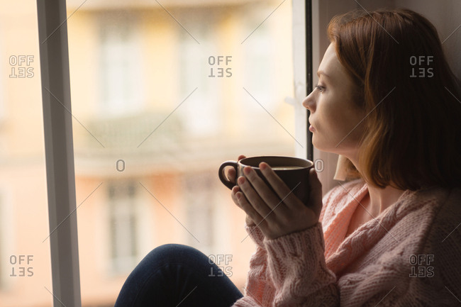 Woman having coffee while looking through window at home