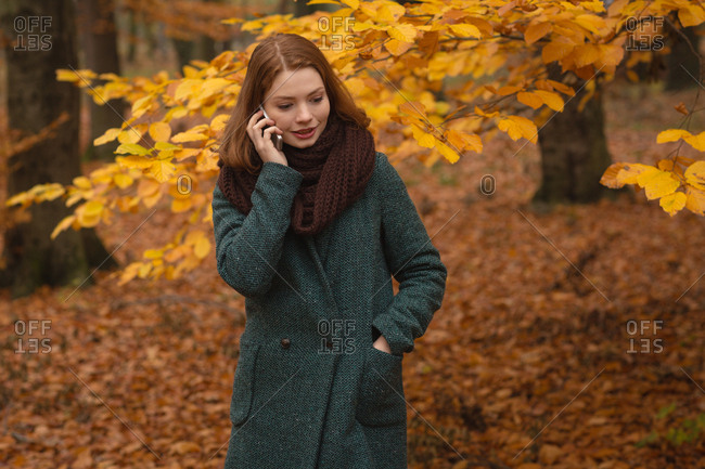 Woman talking on mobile phone in the park during autumn
