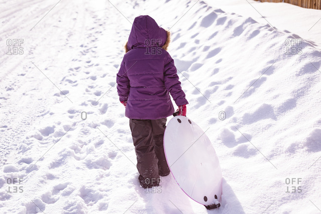 Rear view of girl walking with sled during winter