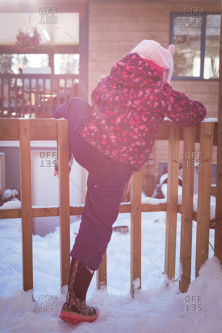 Rear view of girl climbing a fence during winter