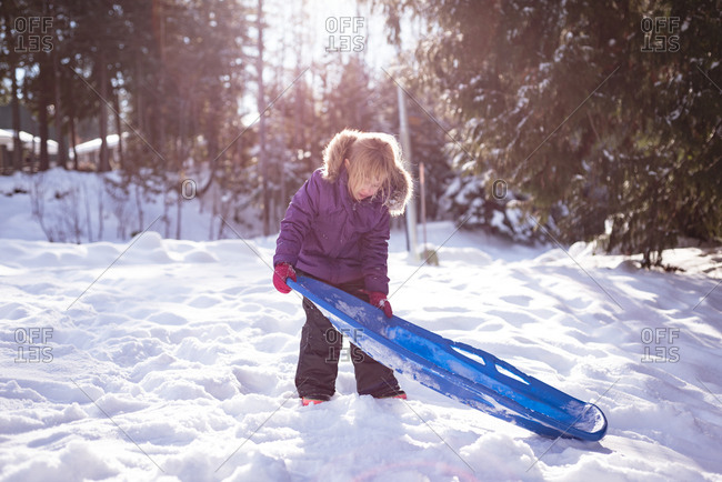 Cute girl holding sled in snow during winter