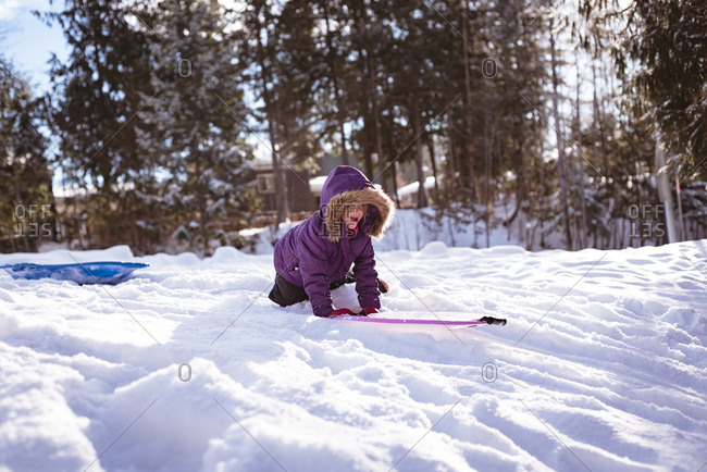 Cute girl playing with sled in snow during winter