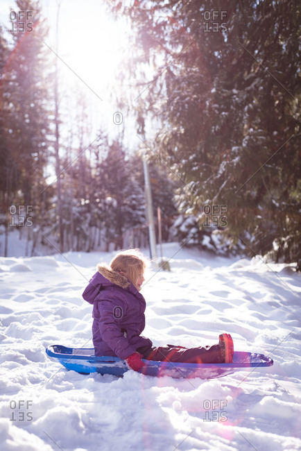 Cute girl playing in sled during winter