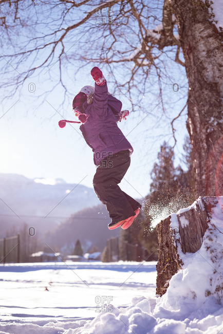 Carefree girl playing in snow during winter