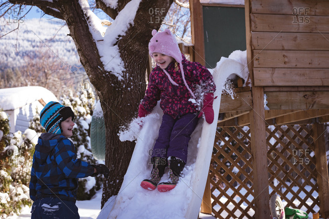 Siblings playing in snow covered playground during winter
