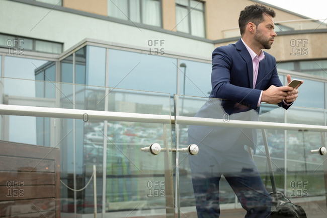 Thoughtful businessman leaning on glass railing