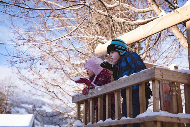 Siblings playing with snow in playground during winter