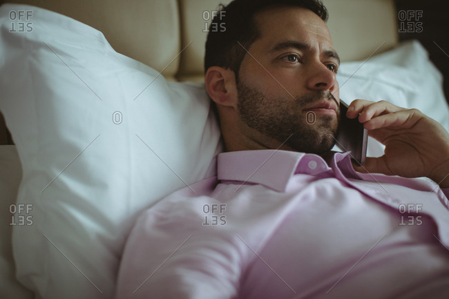 Businessman talking on mobile phone in hotel room