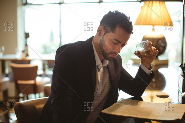 Businessman reading newspaper while having a glass of whisky in hotel