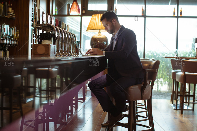 Businessman using laptop near counter in hotel