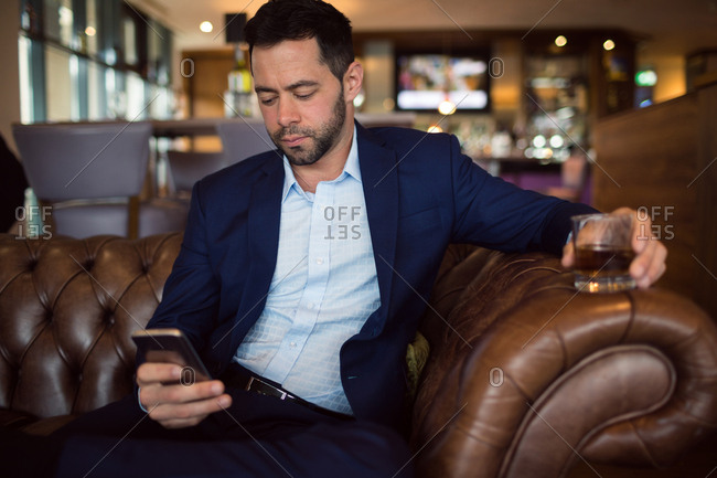 Businessman using while having whisky in hotel
