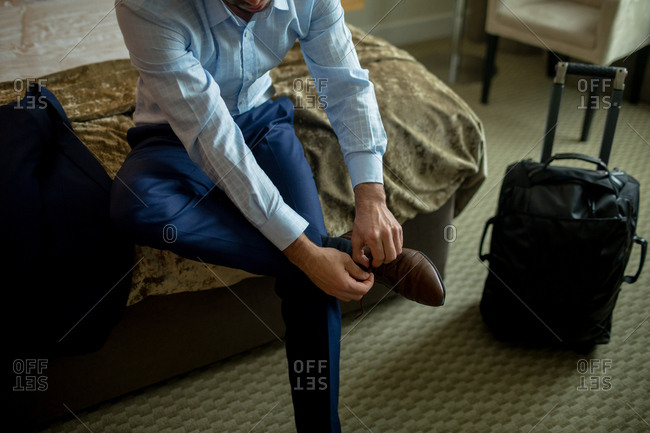 Businessman tying shoes laces in hotel room