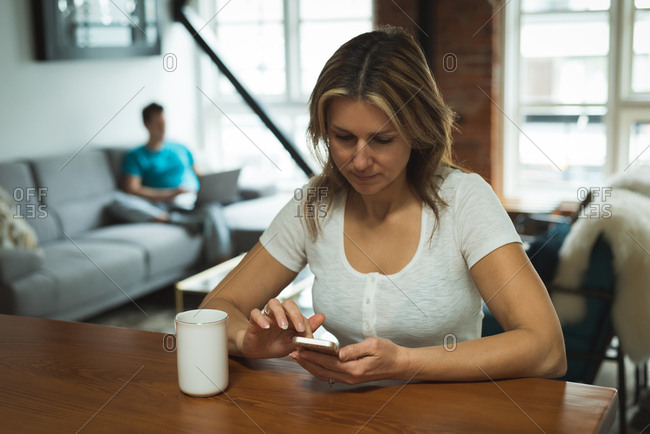 Woman using mobile phone in living room at home