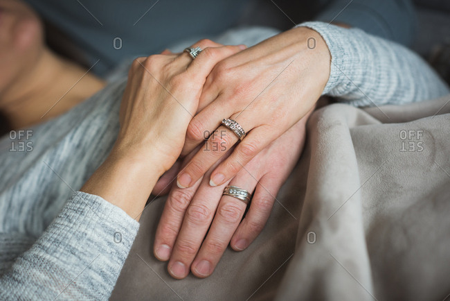 Couple holding hands in living room at home