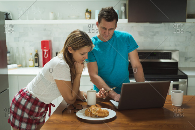 Couple using laptop and mobile phone in kitchen art home
