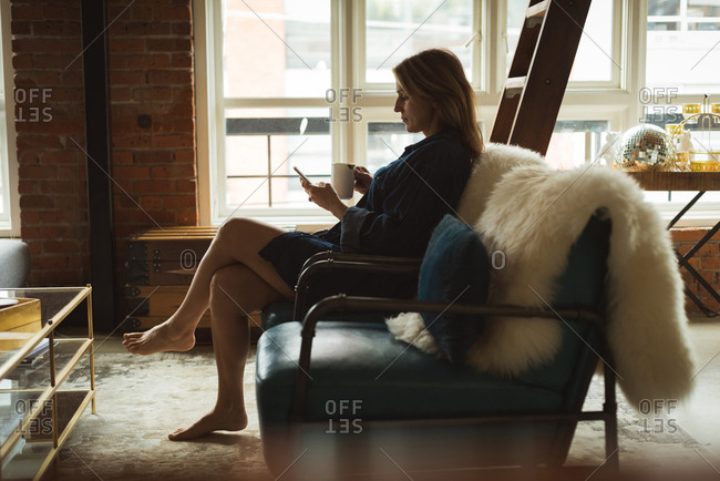 Woman using mobile phone while having coffee at home
