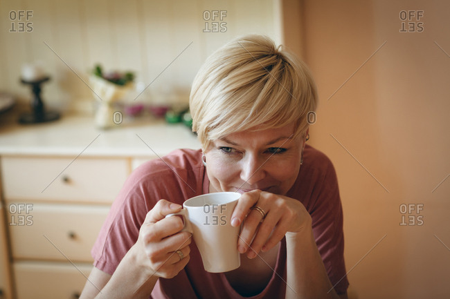 Smiling woman having coffee at home