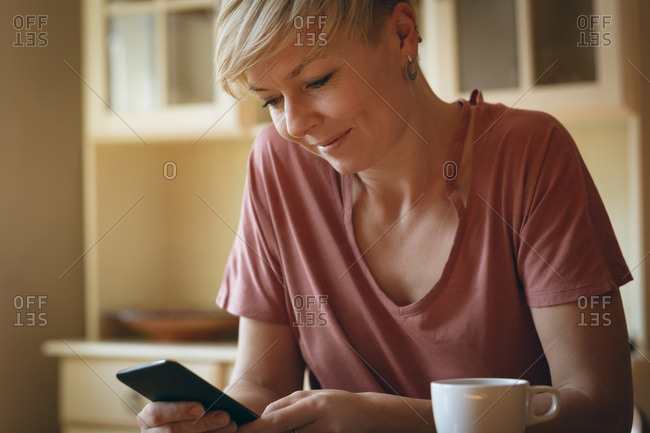 Smiling woman using mobile phone at home