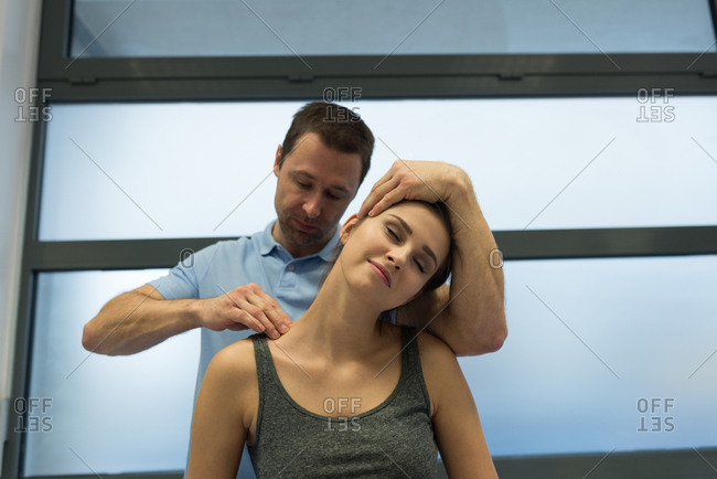 Physiotherapist giving massage to woman in clinic