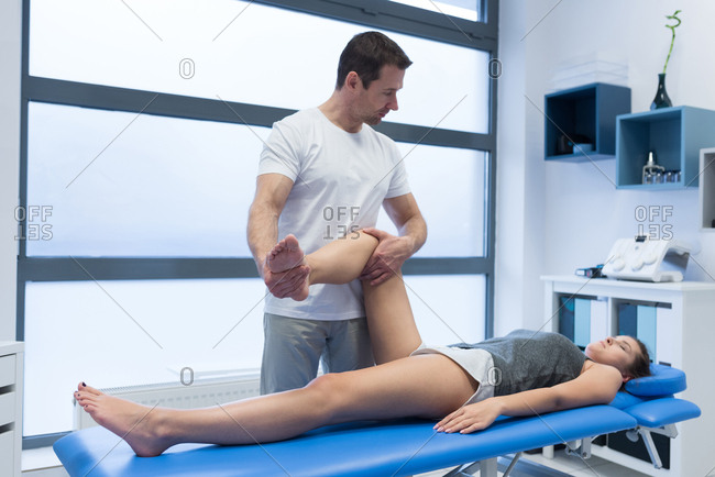 Physiotherapist giving leg massage to woman in clinic