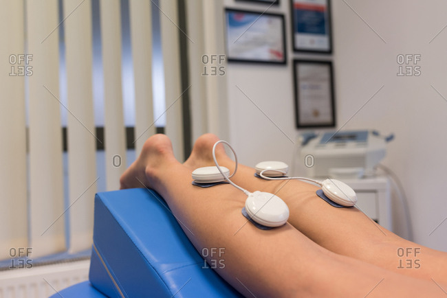 Woman lying with electrode pads on leg in clinic