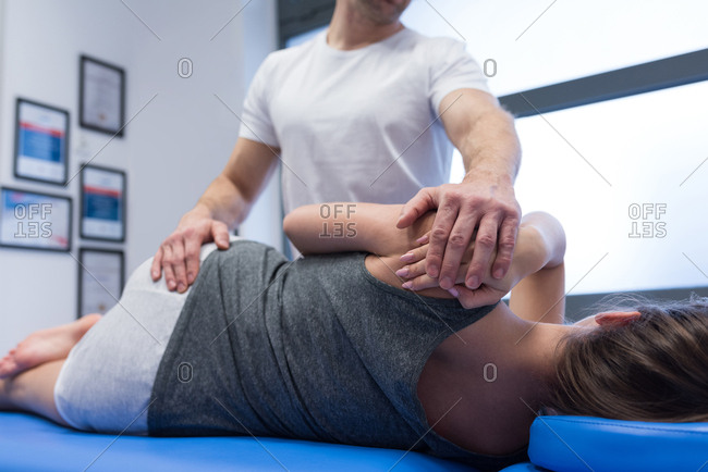 Physiotherapist giving back massage to woman in clinic
