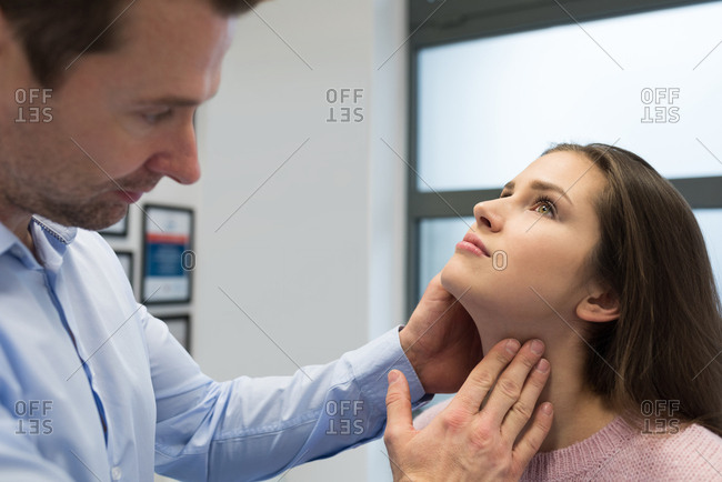 Physiotherapist giving neck massage to woman in clinic