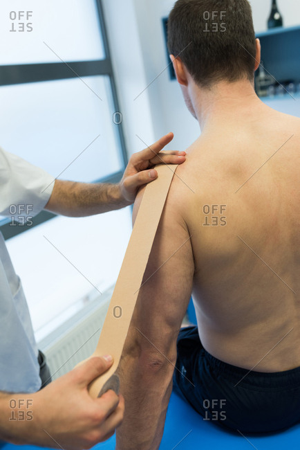 Physiotherapist applying bandage on patient shoulder in clinic