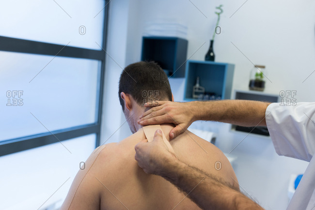 Physiotherapist applying bandage on patients back in clinic