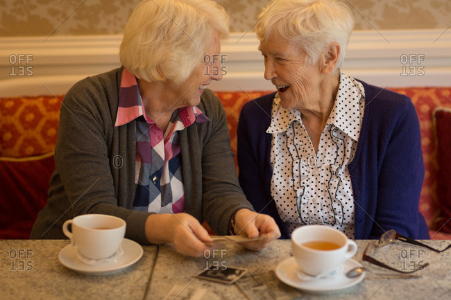 Senior friends interacting with each other while having coffee at home
