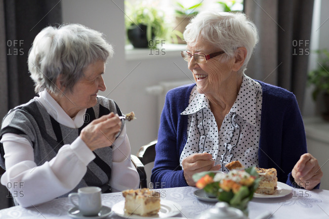 Senior friends interacting witch each other while having breakfast at home