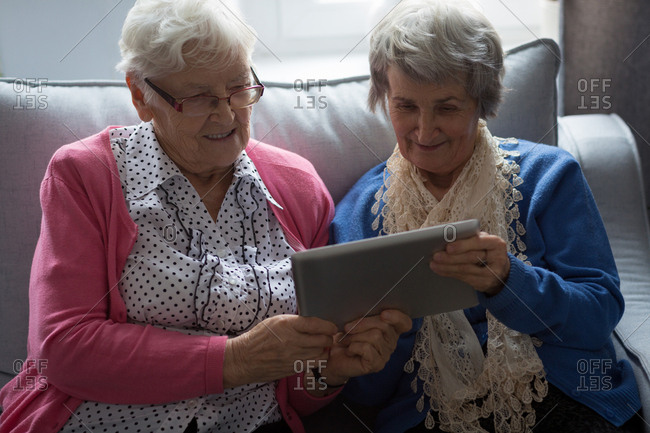 Senior friends using digital tablet at home