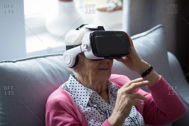 Senior woman using virtual reality headset at home