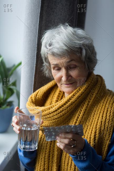 Senor woman having medicine at home