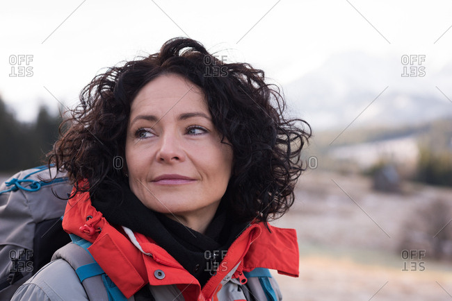 Thoughtful woman standing with backpack during winter