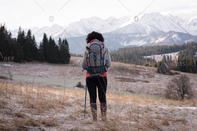 Rear view of woman standing with backpack and hiking pole during winter