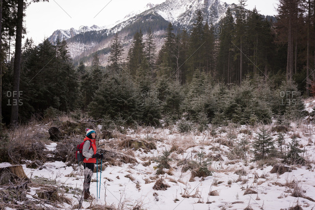 Thoughtful woman standing with backpack and hiking pole during winter
