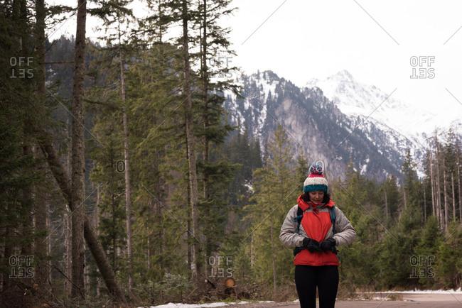 Woman adjusting backpack belt on waist during winter