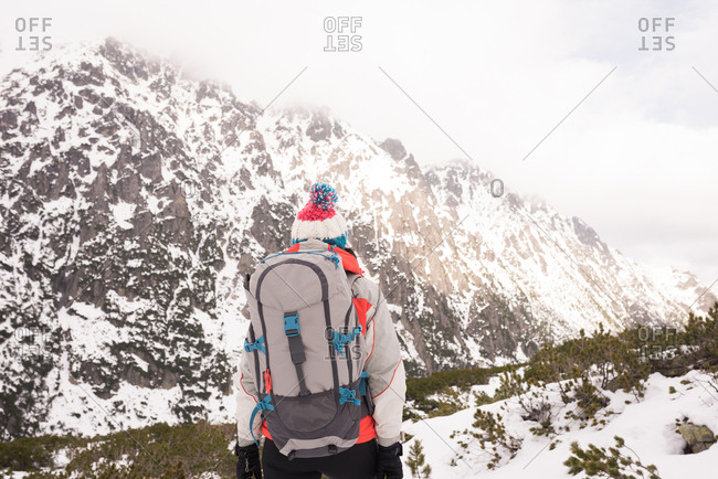 Rear view of woman standing with backpack during winter