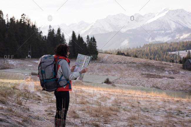 Woman looking at map while hiking during winter