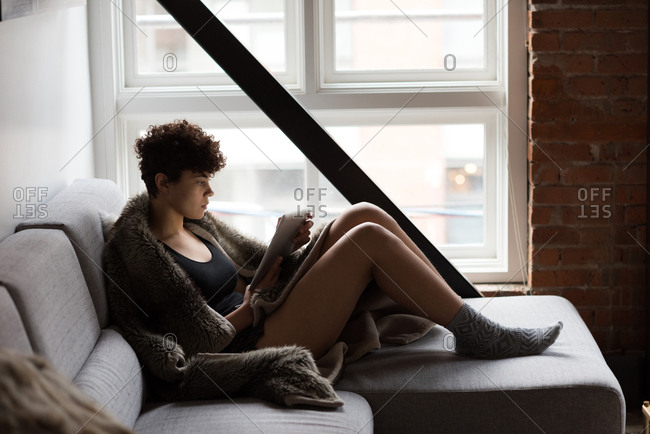 Beautiful woman using digital tablet while relaxing on sofa at home